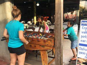 Isabel jugant amb nens al futbolín al carrer principal de Tortuguero